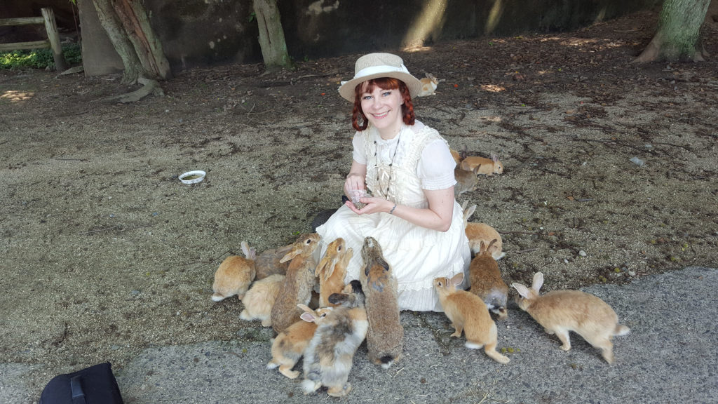 Author surrounded by rabbits on Bunny Island, Japan